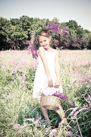 Beautiful blond girl holding basket with flowers photo