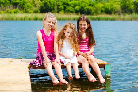 Three little barefoot friends sit on wooden bridge photo