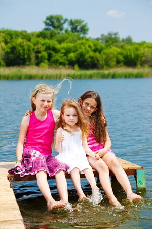 little girl barefoot: Kids sitting on the river bridge in a sunny day
