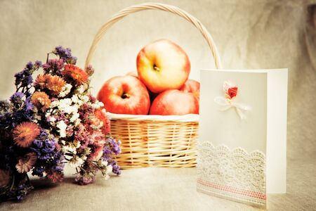Apples in basket and wild flowers with blank greeting card photo