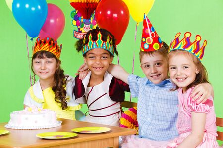 children party: Four friends at the birthday party, embracing