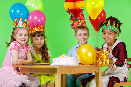 Girls and boy in party hats and crowns sit at the table photo