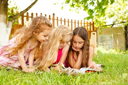Curious children reading book in the outdoor photo