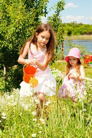 Zwei Schwestern im Garten, der camomiles wässert