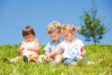 Three kids sit on grass photo