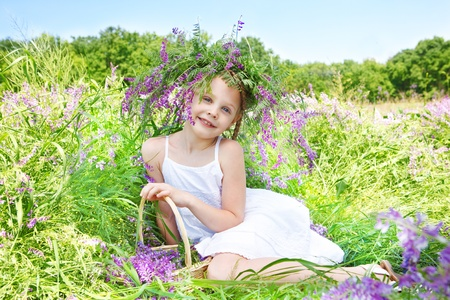 Sweet girl with headwreath on, sitting in the meadow photo