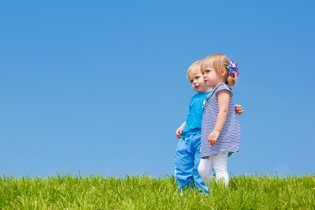 Two kids embracing, gazing afar Stock Photo