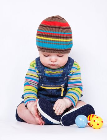 Sweet baby boy in bright clothing sits on the sofa photo