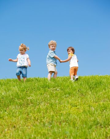 Three lovely toddlers on the hill photo