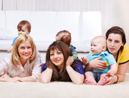 Female friends with kids lying on the carpet Stock Photo - 9863725