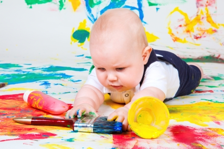 A curious infant lying on the floor and playing with paintbrush photo