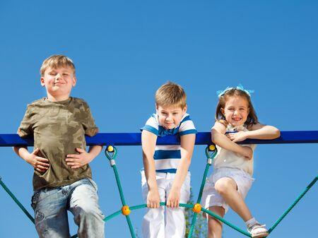 playground children: Three school aged friends climbing the net