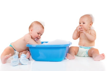 Two baby friends sit beside blue tub  photo