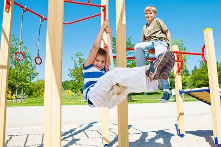 children playground: Cheerful boy swinging on rope