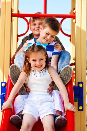 Three little friends on the playground slide Stock Photo - 9978613