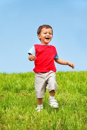Joyful kid running down the green hill photo