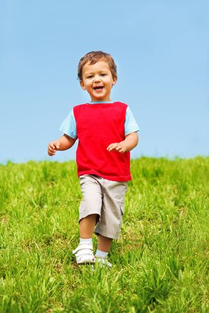 Laughing boy in red t-shirt running photo