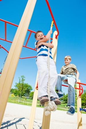 Happy boy swinging on the rope photo