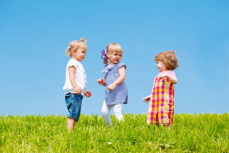 Three Caucasian toddler girls standing on the lawn photo