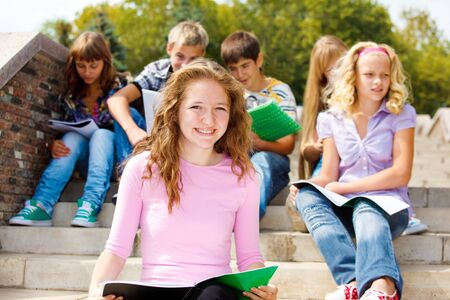 Highschool students with books, sitting on the stairs Stock Photo - 9978615