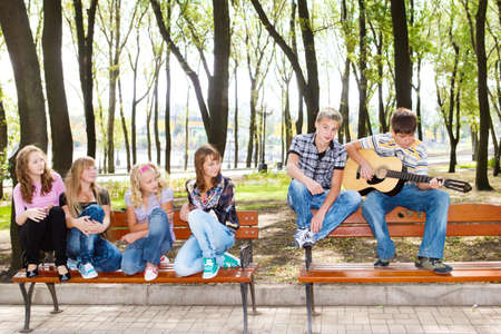 teenage guy: Teenage guy playing guitar, his friends listening Stock Photo