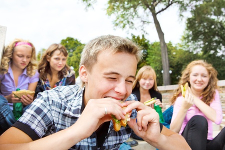 Teen guy biting sanwich photo