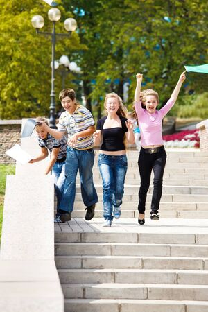 schoolchild: Attractive college students running and throwing their books