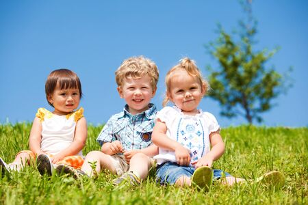 Cheerful kids sit on the green grass photo