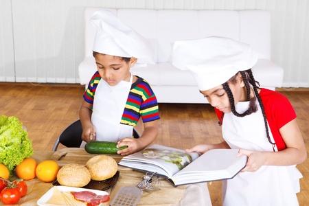 Kinderen lezen van koken boek en het maken van salade