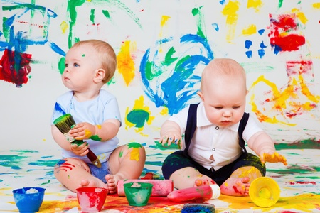 Two babies playing with paints photo
