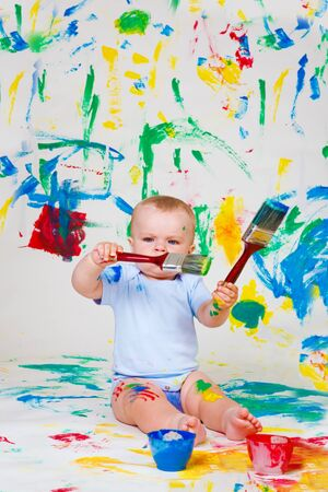 Lovely baby playing with paintbrushes photo