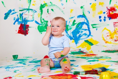 Cheerful baby boy with paint spots on arms and legs photo