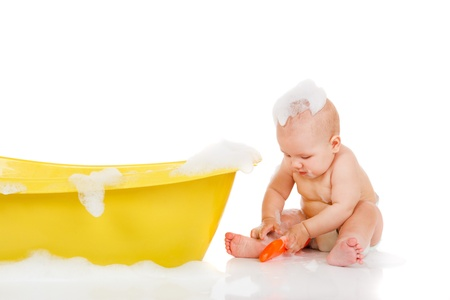 Cute baby with foam on head sits beside yellow bath Stock Photo