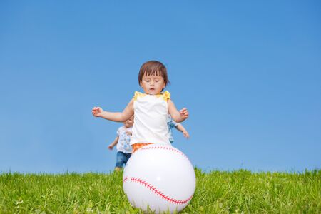 Toddlers running downhill and catching the ball photo
