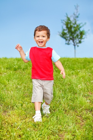 Healthy exciting kid running down the hill photo