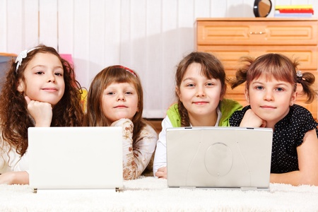 Four girls lying on floor with two laptops Stock Photo - 10369681