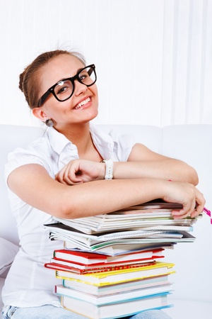 Happy female student in glasses holding books photo