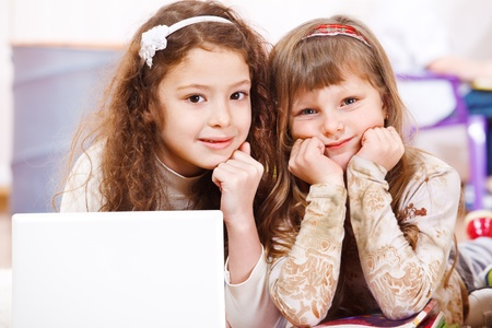 Two school aged girls lying beside laptop photo