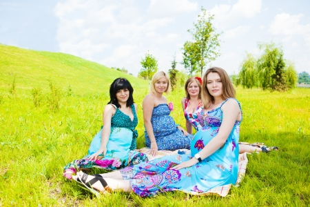 pregnant girl: Four pregnant female friends relaxing in park