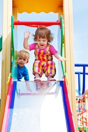 niños en area de juegos: Dos bebés felices listo para deslizar hacia abajo Foto de archivo