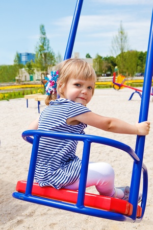 Toddler  girl swinging at the playground photo