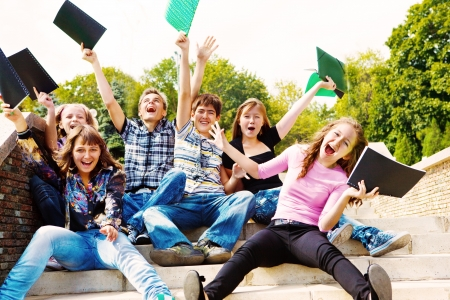 school friends: Teenage guys and girls with books in hands, shouting Stock Photo