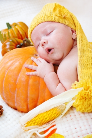 Newborn baby sleeping on a pumpkin photo