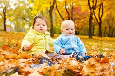Sweet kids sitting on the autumn leaves photo