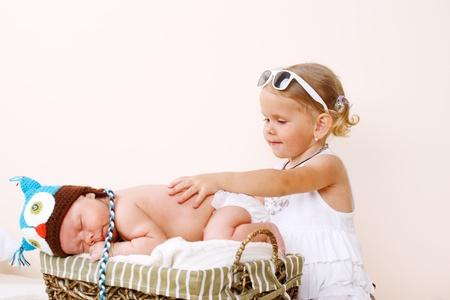 Sweet toddler girl and newborn baby sleeping