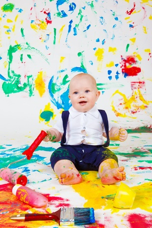 Cheerful baby busy with painting photo