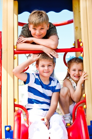Two school aged boys and girl on the playground photo