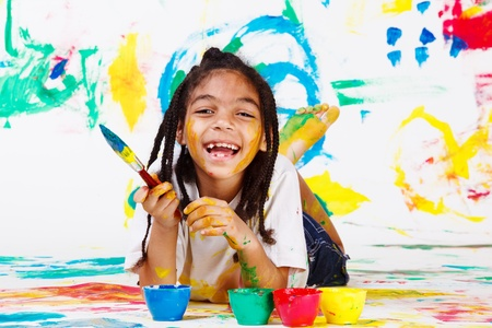 Laughing African American girl lying with a paintbrush Stock Photo - 10428009