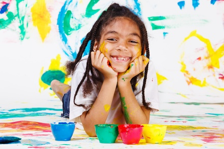 African American kid playing with finger paints photo