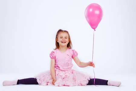 Happy girl holding pink balloon in hand photo